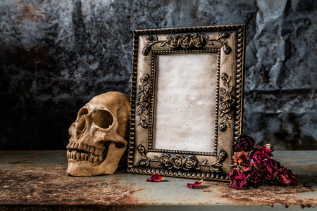 Still life photography with photo frame and human skull