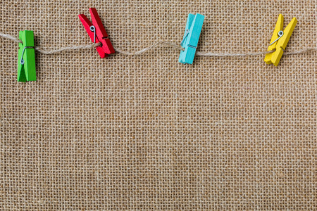 linens: Sackcloth texture background with colorful wood clips Stock Photo