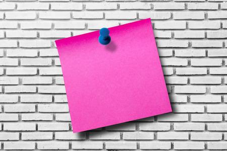 papel de notas: Papel de nota rosa sobre fondo de pared de ladrillo blanco Foto de archivo