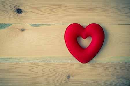 Red heart on wood board background with vintage tone Фото со стока