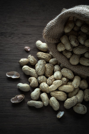 Peanuts in gunny bag on wood board back ground with dark mood photography, Still life with peanuts on wood board
