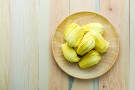 Jackfruit in wood dish on wood table, top view Фото со стока