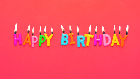 Happy birthday colorful candles on pink paper background Фото со стока