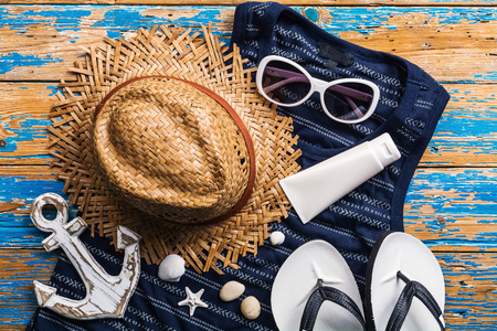 Beach accessories on blue distressed wood table, Vacation and travel items