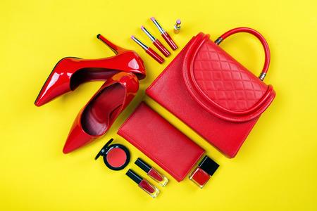 Vista aérea de artículos de belleza esenciales, vista superior del bolso de cuero rojo, zapatos rojos y cosméticos. Foto de archivo