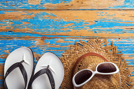 White Beach flip flop, sunglasses and straw hat on blue distressed wooden table