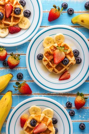Waffles with fresh fruit and caramel on blue table, top view Archivio Fotografico