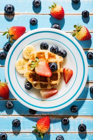 Waffles with fresh fruit on blue table, top view