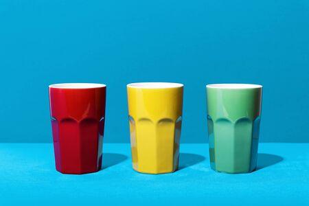 Colorful ceramic mugs on blue background