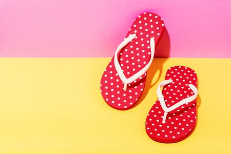 Red beach flip flops on colorful background