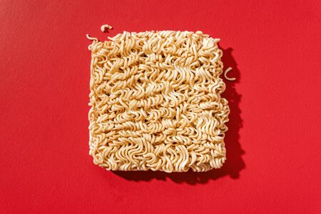 Instant noodles on red paper background