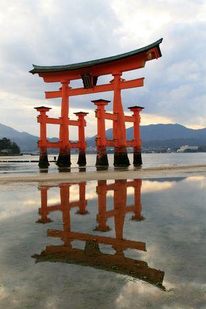 hiroshima: miyajima temple gate reflecting of the low tide sand banks in hiroshima prefecture japan