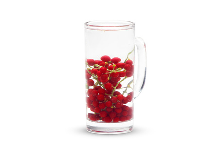 Picture of red berry in a glass with water. Isolated on white background.