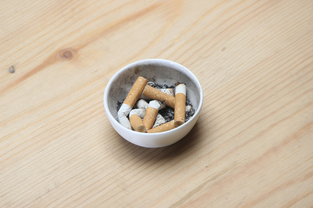 Cigarette in white ashtray on wooden background. Stock Photo