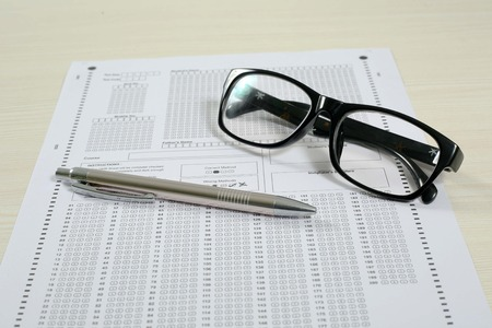 Picture of omr sheet, glasses and pen. Isolated on white background. Reklamní fotografie