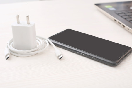 Picture of phone, adapter and USB cable. Isolated on wooden background. 写真素材