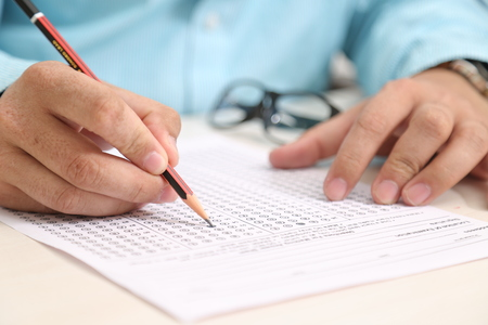 Man is filling OMR sheet with pencil.