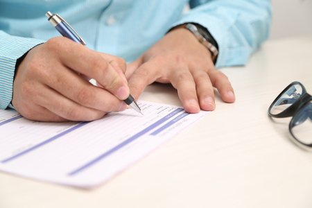 Man is filling form with pen. Picture of glasses on the table.
