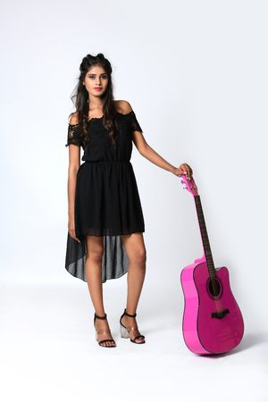 Young girl is standing on the floor with holding pink guitar in hand. Isolated on white background.