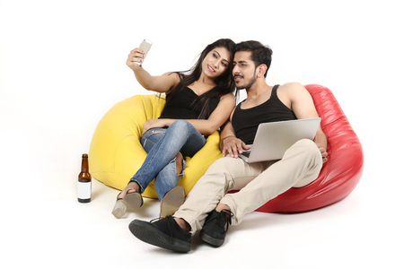 Young boy and girl is sitting on bean bag couch with laptop and juice bottle. Couple is taking selfie in phone. Isolated on white background. Stock Photo