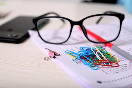 Image d'une feuille OMR, d'une épingle en papier, de lunettes, d'un stylo et d'un téléphone. Isolé sur fond en bois. Banque d'images