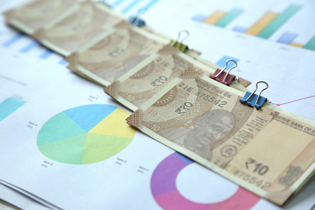 Picture of multiple new pack of Indian 10 Rupee notes with chart paper. Isolated on wooden background. 版權商用圖片