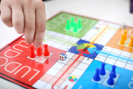 The game of ludo is very mindly game. Man is playing ludo. Stock Photo