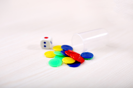Picture of ludo game tokens with dice on the wooden table.