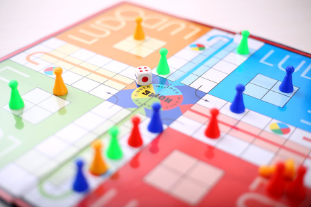Different colors ludo tokens and dice on the ludo game. Stock Photo