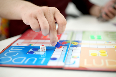 Picture of hand is playing ludo with blue ludo tokens. Stock Photo