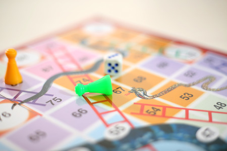 Picture of snakes and Ladders Game with tokens and dice.