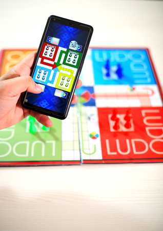 Man is playing ludo in phone with ludo board on the table. Stock Photo