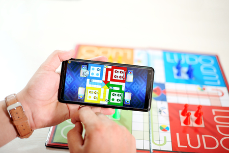 Man is showing ludo game in phone. Picture of ludo board game on the table.
