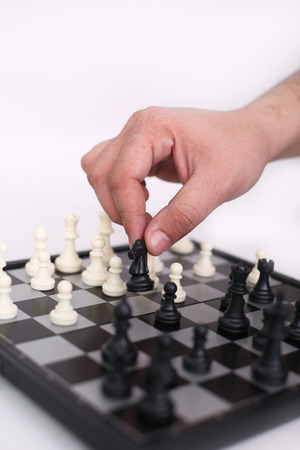 Man hand is playing chess. Isolated on the white background.