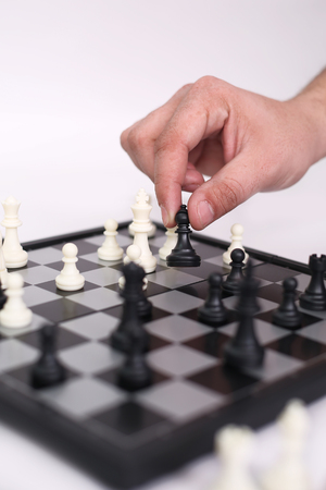 Hand is playing chess. Isolated on the white background.