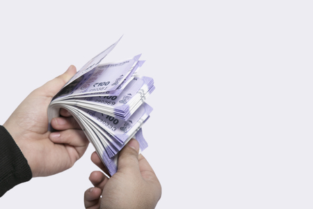 100 Indian currency in hand. Isolated on the white background Stok Fotoğraf