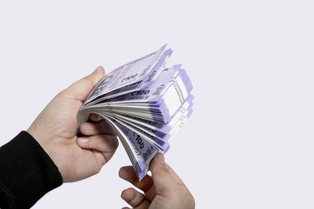 Indian one hundred rupee notes in hand. Isolated on the white background. Stok Fotoğraf