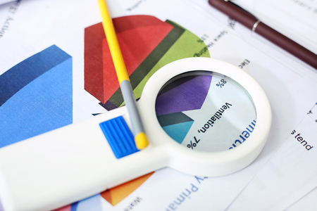 Picture of pen, pencil and magnifying glass on the financial paper.