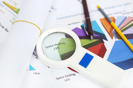Picture of roll paper, pen, pencil and magnifying glass on the chart paper.