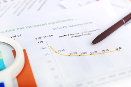 portrait of pen and magnifying glass on the financial paper.