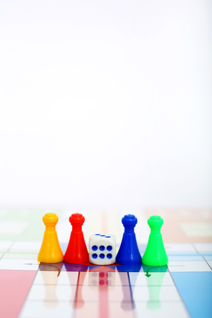 Picture of different color pawns with dice.