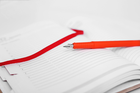 Picture of pen on the open diary. Isolated on the white background.