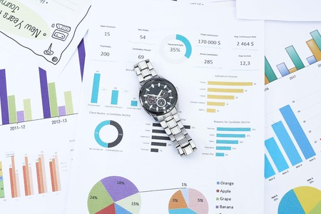 Picture of wristwatch on the financial paper. Imagens
