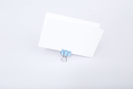 Picture of white greeting card with attach paper clip. Isolated on the white background. Reklamní fotografie