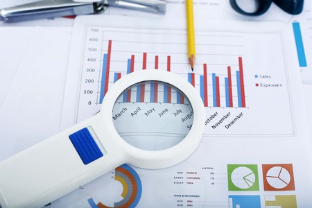 Picture of financial paper, pen and magnifying glass.