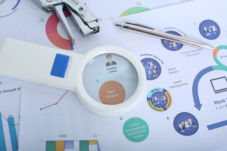 Picture of pen, stapler and magnifying glass on the financial paper. Imagens