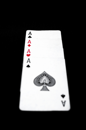 Picture of four aces poker play card. Isolated on the black background.