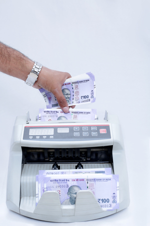 Portrait of hand putting Indian currency in cash counting machine. Isolated on the white background.
