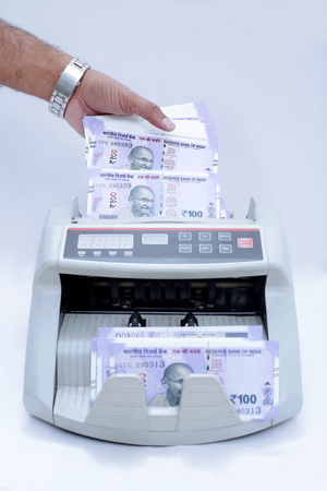 Picture of man hand is putting new 100 rupees notes in cash counting machine. Isolated on the white background. Stock Photo