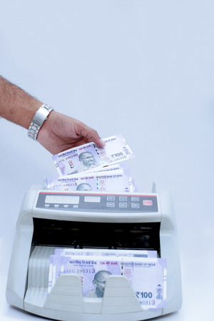 Picture of man hand is putting new Indian 100 rupees currency in cash counting machine. Isolated on the white background.